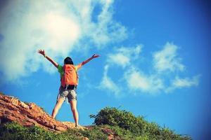 animando mochilero joven disfruta de la vista en el pico de la montaña foto