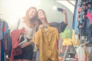 jóvenes amigas rubias y marrones disfrutan en una tienda de ropa de segunda mano
