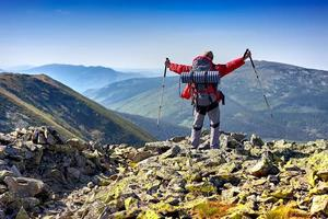 Hiker with backpack standing in mountains and enjoying the v photo