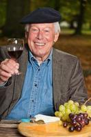 uomo francese che gode del vino rosso e del formaggio nella foresta di autunno.