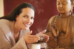 Brunette woman enjoying joss stick's scent buddha statue in background