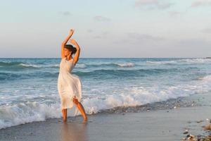Young woman enjoys a walk at the beach at dusk.