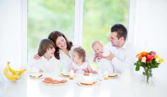 Familia joven con tres hijos disfrutando del desayuno cerca de una ventana grande foto