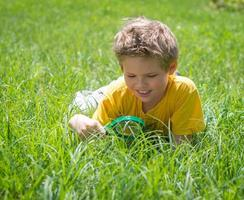 Kid with magnifying glass outdoors. Happy boy enjoying sunny summer.