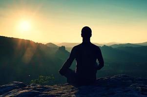 excursionista en posición en cuclillas sobre una roca, disfrute del paisaje dybreak