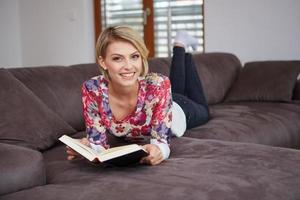 Mujer disfrutando leyendo un libro en casa tumbado en el