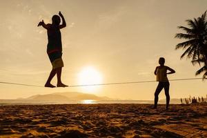 teenagers balance on slackline silhouette