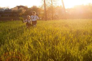 Two little girls running in tall grass field photo