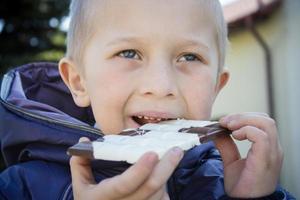 Boy eating chocolate photo