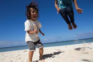 Children jumping on the beach photo