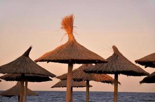 Sombrillas de playa al atardecer en Vama Veche, Rumania