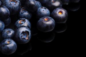 Several whole blueberries isolated on black corner