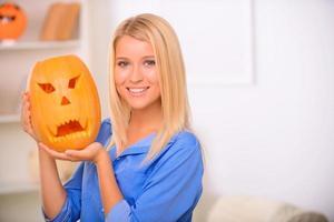 Elated girl holding pumpkin photo