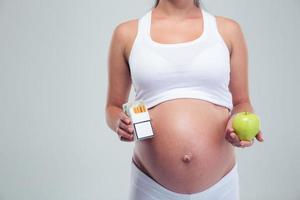 mujer embarazada elegir cigarrillos beetwin y manzana foto