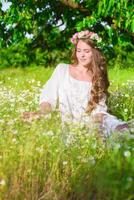 Girl with long hair on the field with daisies photo