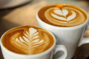 Two mugs of latte having leaf and heart latte art