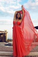pretty woman in luxurious red dress posing at park
