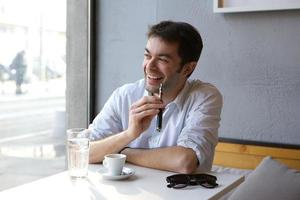Young man sitting indoors enjoying electronic cigarette photo