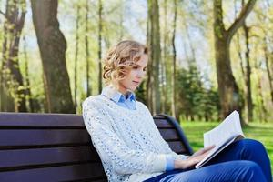 student girl reading book in park, science and education concept
