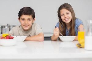 Hermanos jóvenes sonrientes disfrutando del desayuno en la cocina foto