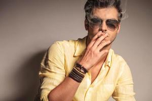 cool fashion man with sunglasses enjoying his cigarette photo