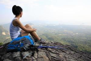 senderismo mujer disfruta de la vista en el pico de la montaña foto
