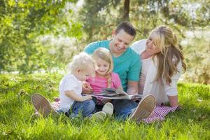joven familia disfruta leyendo un libro en el parque