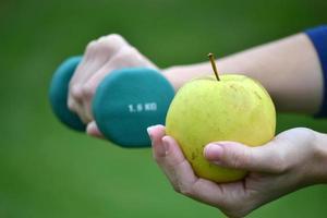mujer con pesas y manzana verde foto