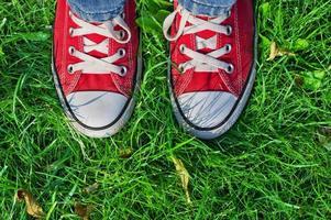 Feet in sneakers in green grass photo