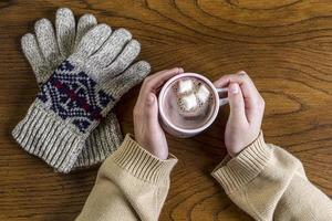 Warming the hands with hot cocoa.