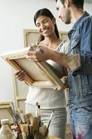 Pareja mirando lienzos en artista studio foto