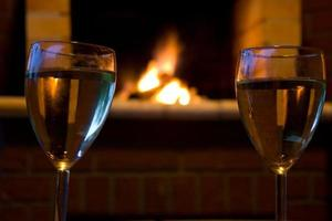 Glasses of wine in front of a fireplace