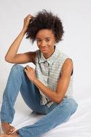 Happy black woman sitting on floor photo