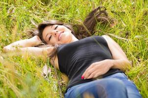 beautiful brunette young girl resting on green grass photo