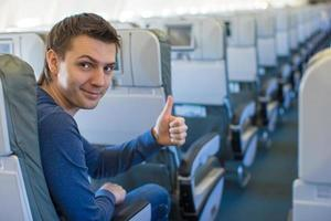 Happy man showing thumbs up inside the aircraft photo