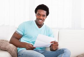 Happy Young Man Looking At Paper