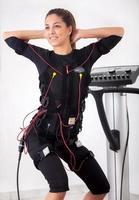 woman exercise trunk-bending forward  on  electro stimulation ma photo