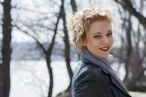 Young curly blond woman smiling
