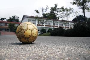 viejo balón de fútbol en la escuela foto