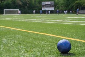 Soccer ball on field with teams, goal, scoreboard in background photo