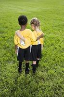vista trasera de niños multirraciales con uniformes de equipos deportivos foto