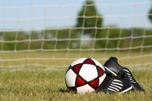 Soccer ball and cleats in front of net