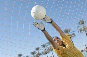 Young female soccer goalie diving to block a goal attempt