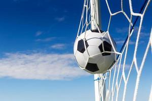 Soccer football in Goal net with sky field.