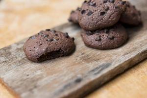 galletas de chispas de chocolate y vaso de leche en placa de madera foto