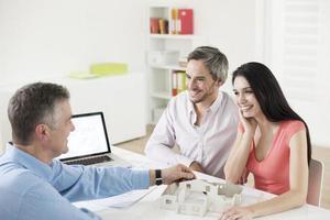 agente de bienes raíces mostrando proyecto de construcción a una pareja