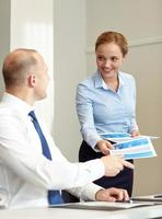smiling woman giving papers to man in office photo