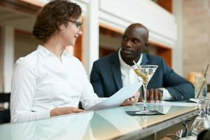 cocktail no balcão com dois empresários em segundo plano