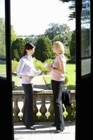 Empresaria en conversación con un colega al aire libre, ver thro foto