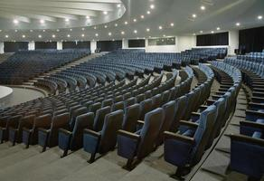 A large auditorium with several rows of blue chairs